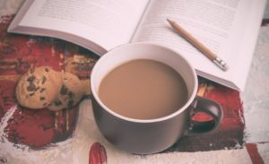 cup of tea and biscuit next to open book