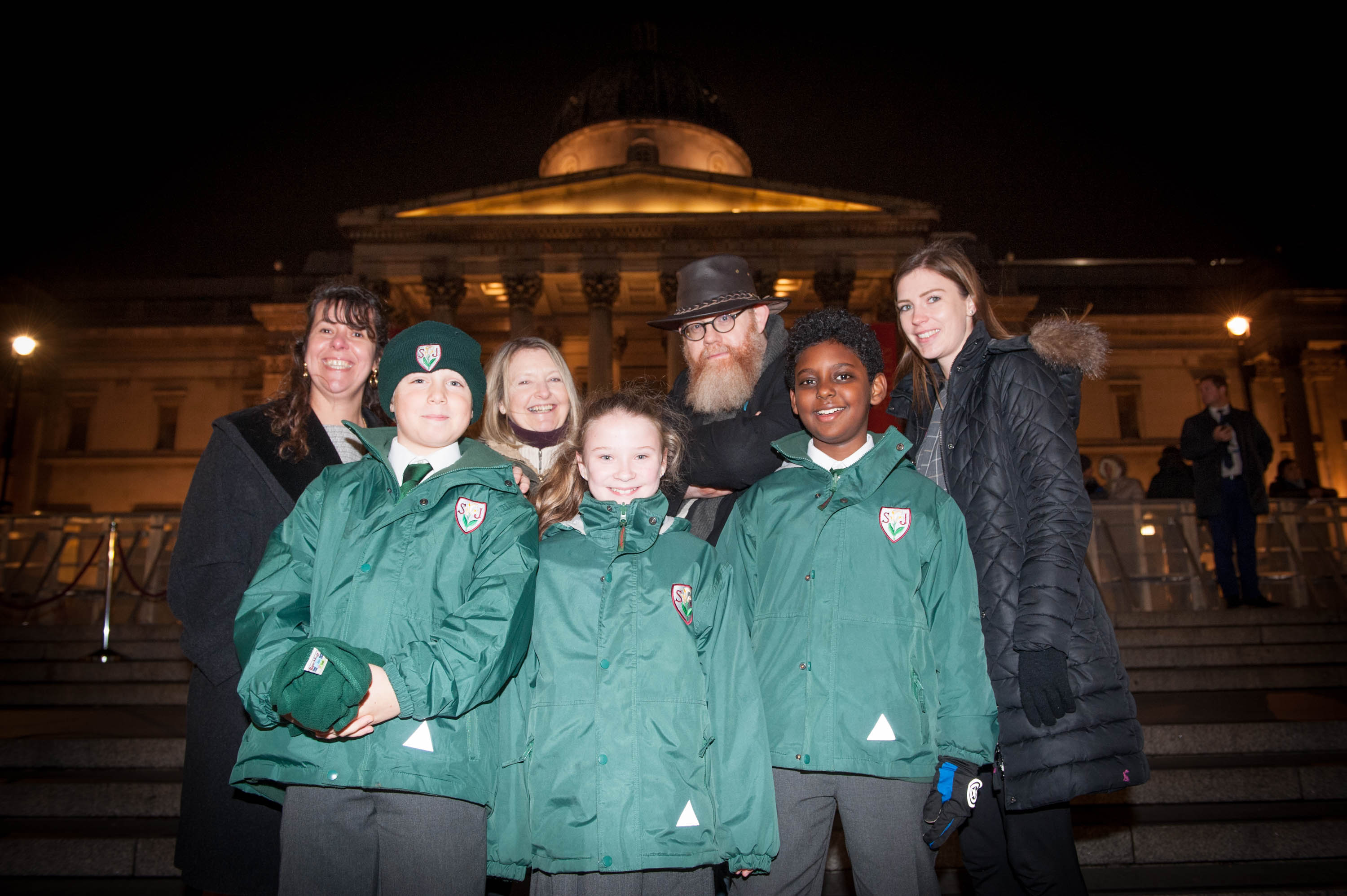 Three children in green school uniform coats in foreground, with teachers and poets smiling behind them.