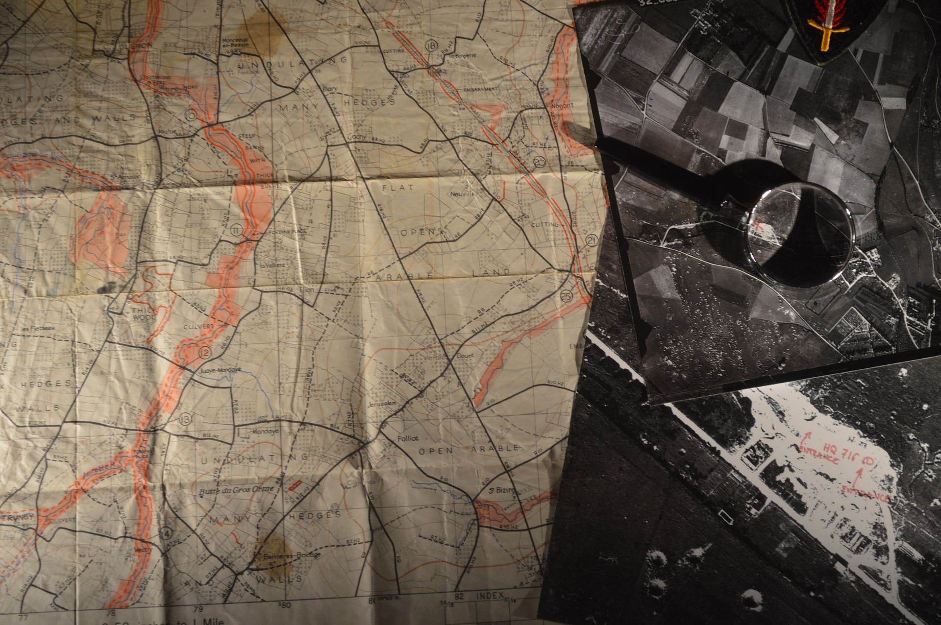 Image of a WWII map alongside aerial black and white photographs of the landscape