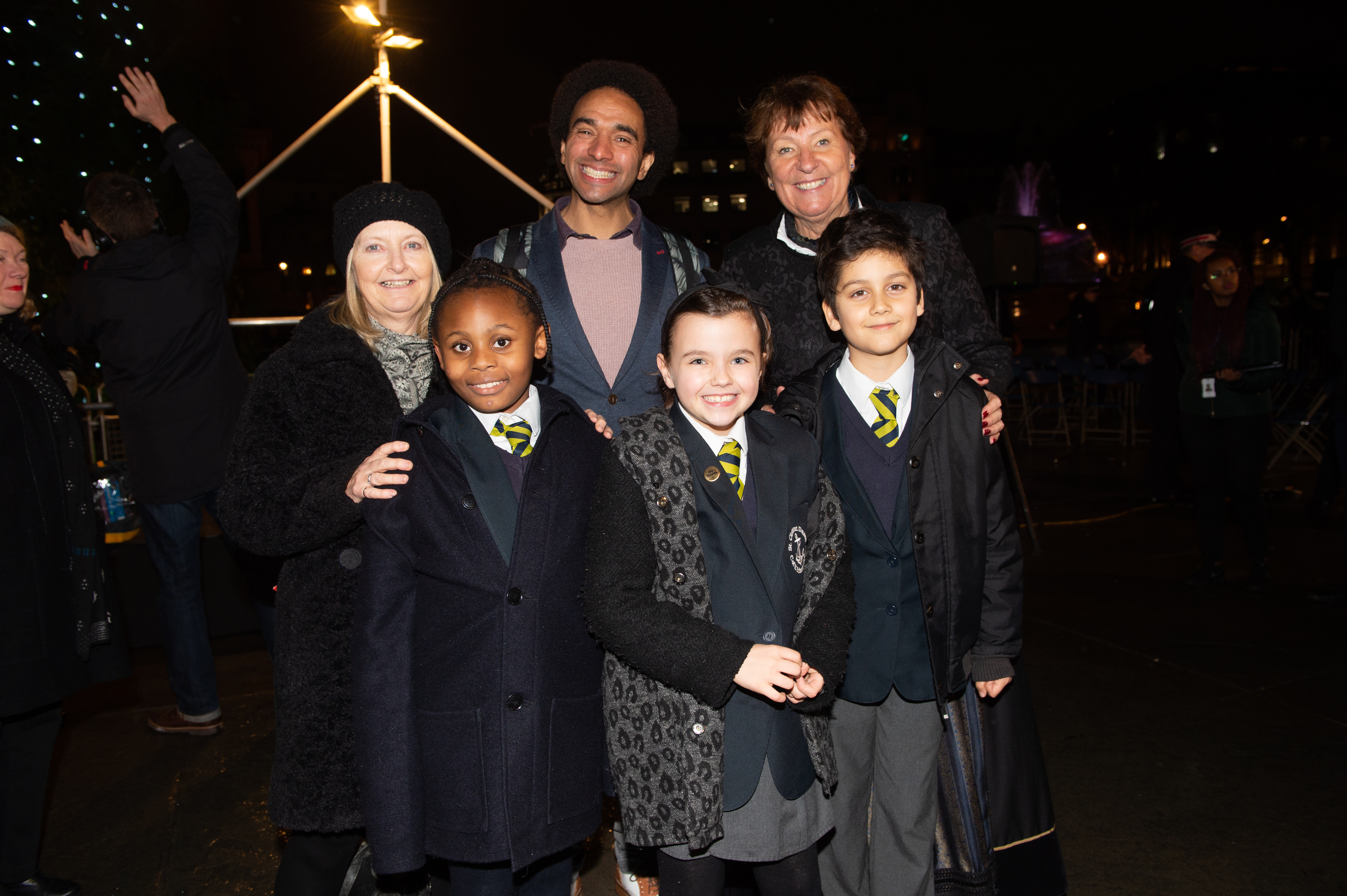 poets, mayor and children stand in front of the trafalgar square Christmas tree smiling
