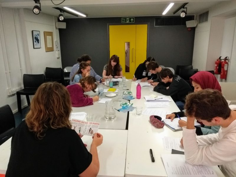 Photo of the workshop group working away downstairs in the basement of The Poetry Café.