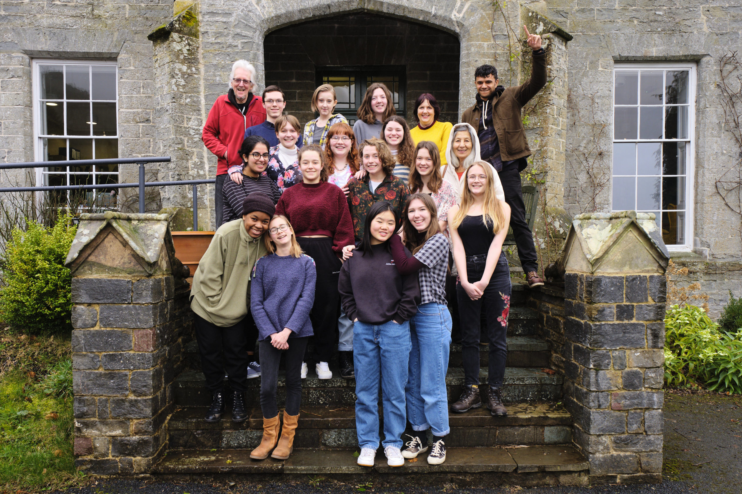 Photo of the 15 Foyle Young Poets standing on steps at Arvon, with poet tutors Raymond Antrobus and Mimi Khalvati, and in loco parentes Fran Pridham and Colin Watts