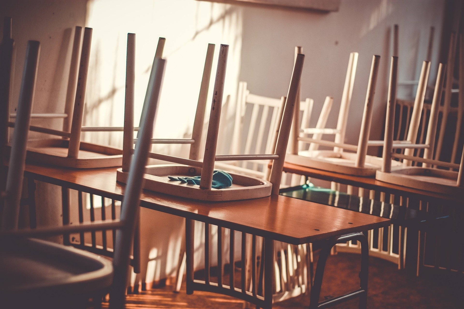 Photo of an empty classroom with the chairs turned over on the tables