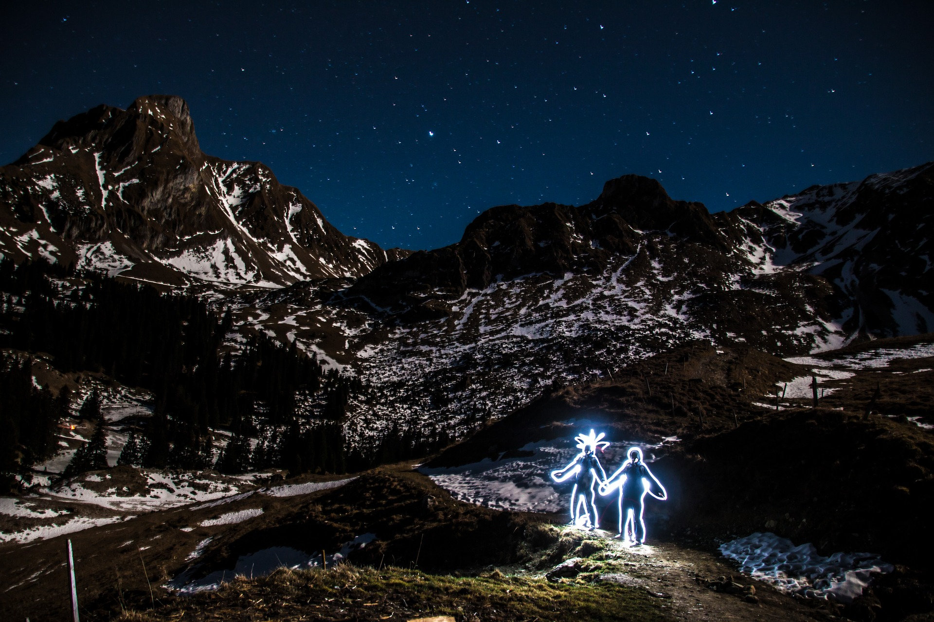 Photo of a snowy mountain range at night, with the stars visible, and in the foreground two figures made out of light looking up at the stars