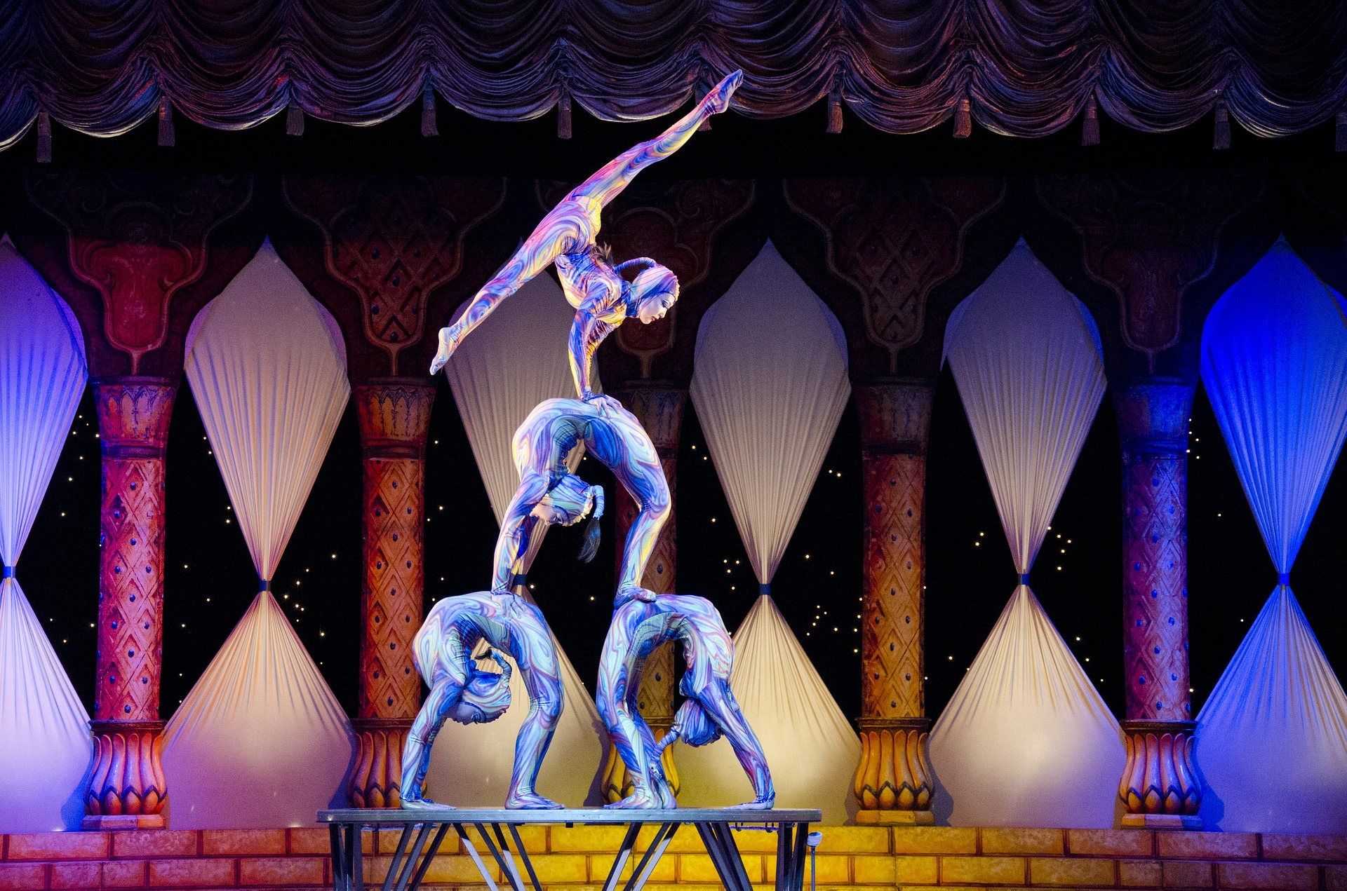 A seemingly psychodelic photo. In the foreground, two acrobats are bent over backwards. On their stomaches, another acrobat stands, also bent over backwards. On top of that acrobat, a fourth acrobat holds themselves up with their arms and their legs in the air doing the splits. All the acrobats are dressed in tight-fitting clothes with blue-purple swirls on. In the background, there are columns with curtains in between that are pinched in the middle, creating a diamond effect.