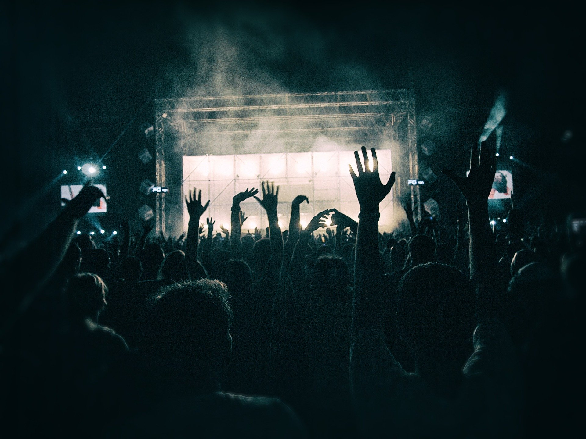 A photo of a crowd at a concert outdoors, On stage there are bright white lights and smoke. People's hands are raised in the foreground.