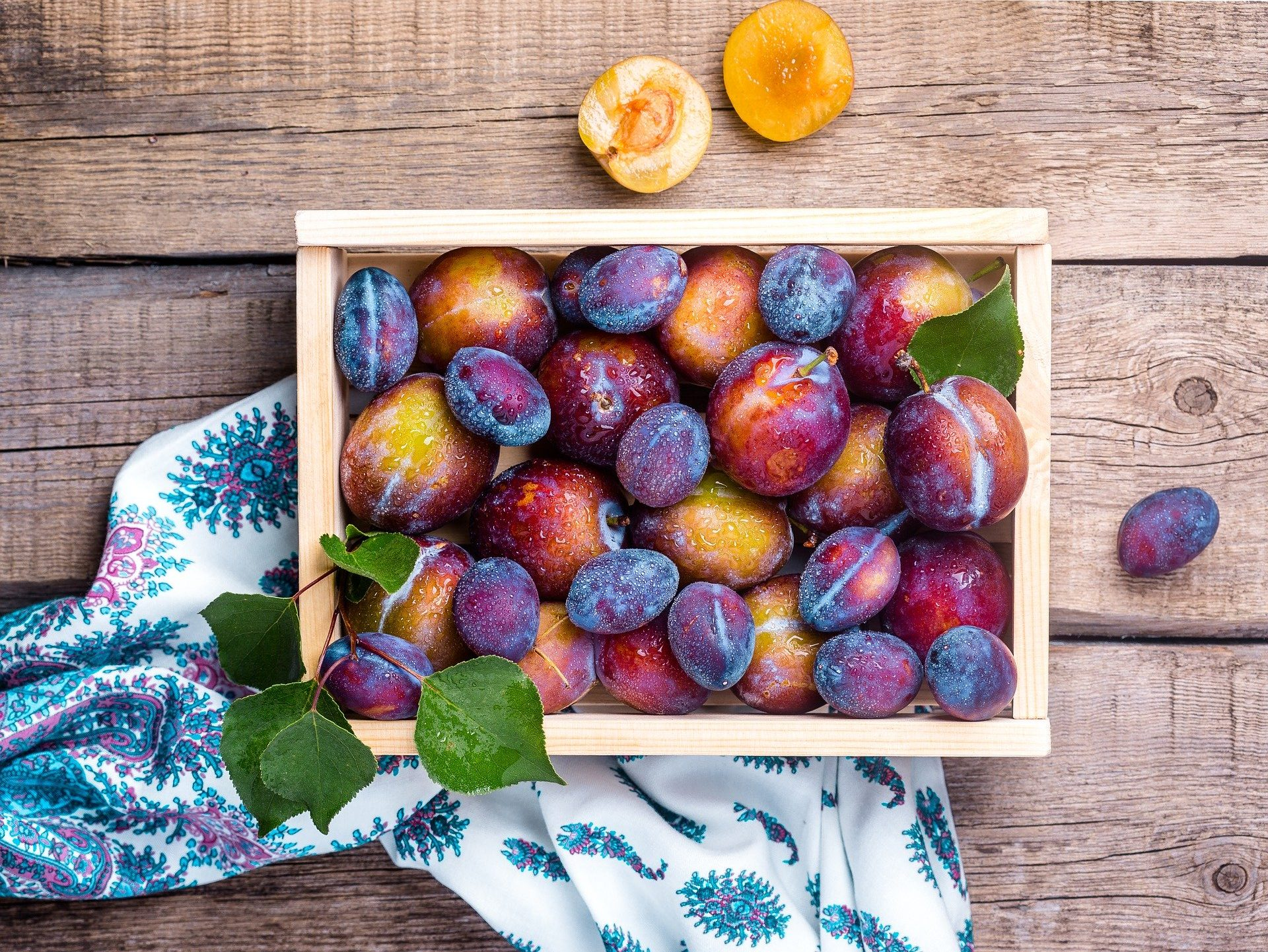 Photo taken from above of a box of cold plums