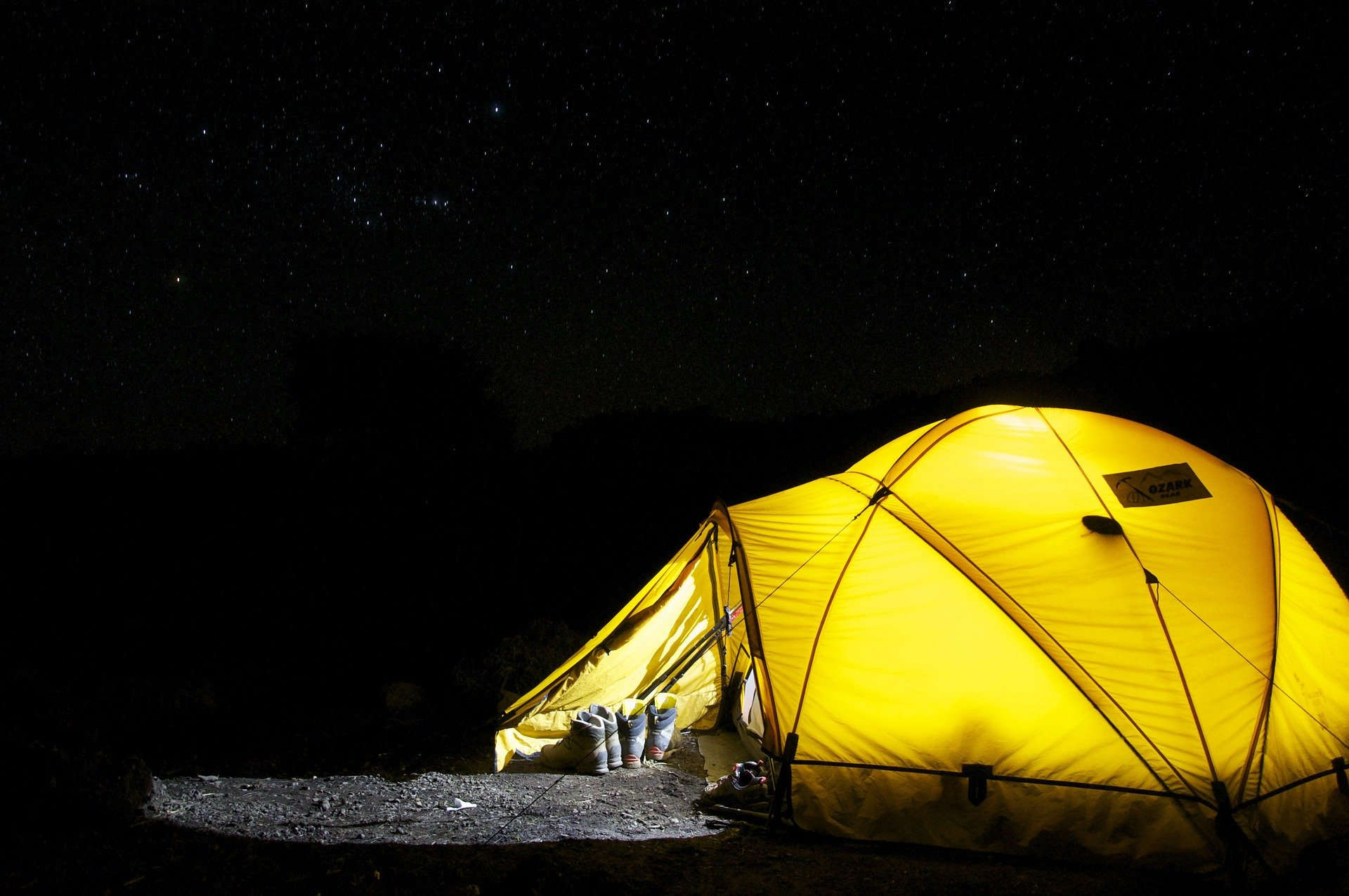 A photo of a yellow tent in pitch black darkness, lit up brightly from the inside.