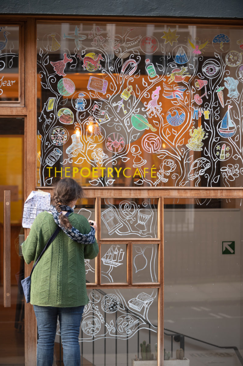 artist decorating windows with poetic images