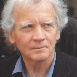 Headshot of David Constantine, looking thoughtfully left, in blue shirt and dark jacket.