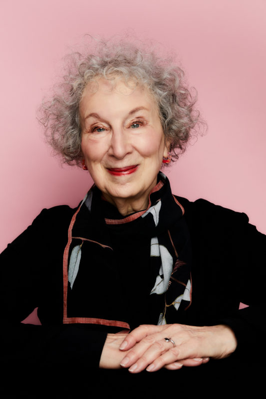 Portrait of Margaret Atwood, smiling, wearing black, against a pink background. Photo by Luis Mora.