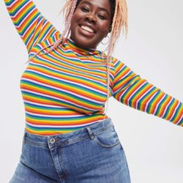 Oluwaseun Matiluko wearing a bright stripy top and smiling with arms open