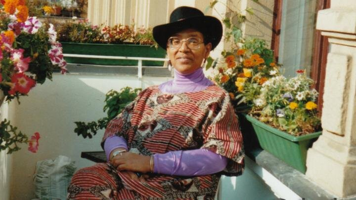 Audre Lorde sits by some flowers wearing a black hat and bright clothes
