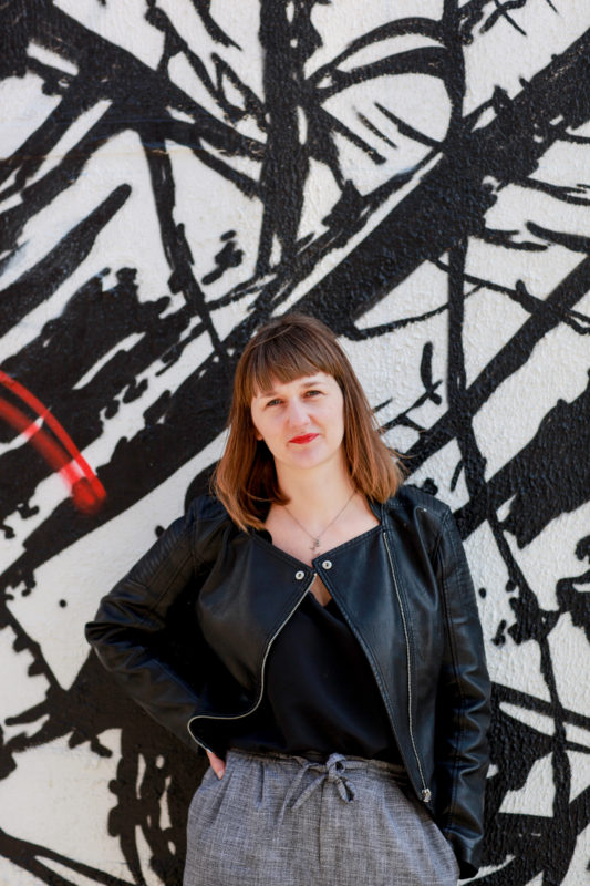 poet Clare Pollard in a leather jacket and black top, against a black, white and red background