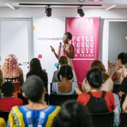 Young Poets Takeover: a young Black woman performs at the front to a full audience