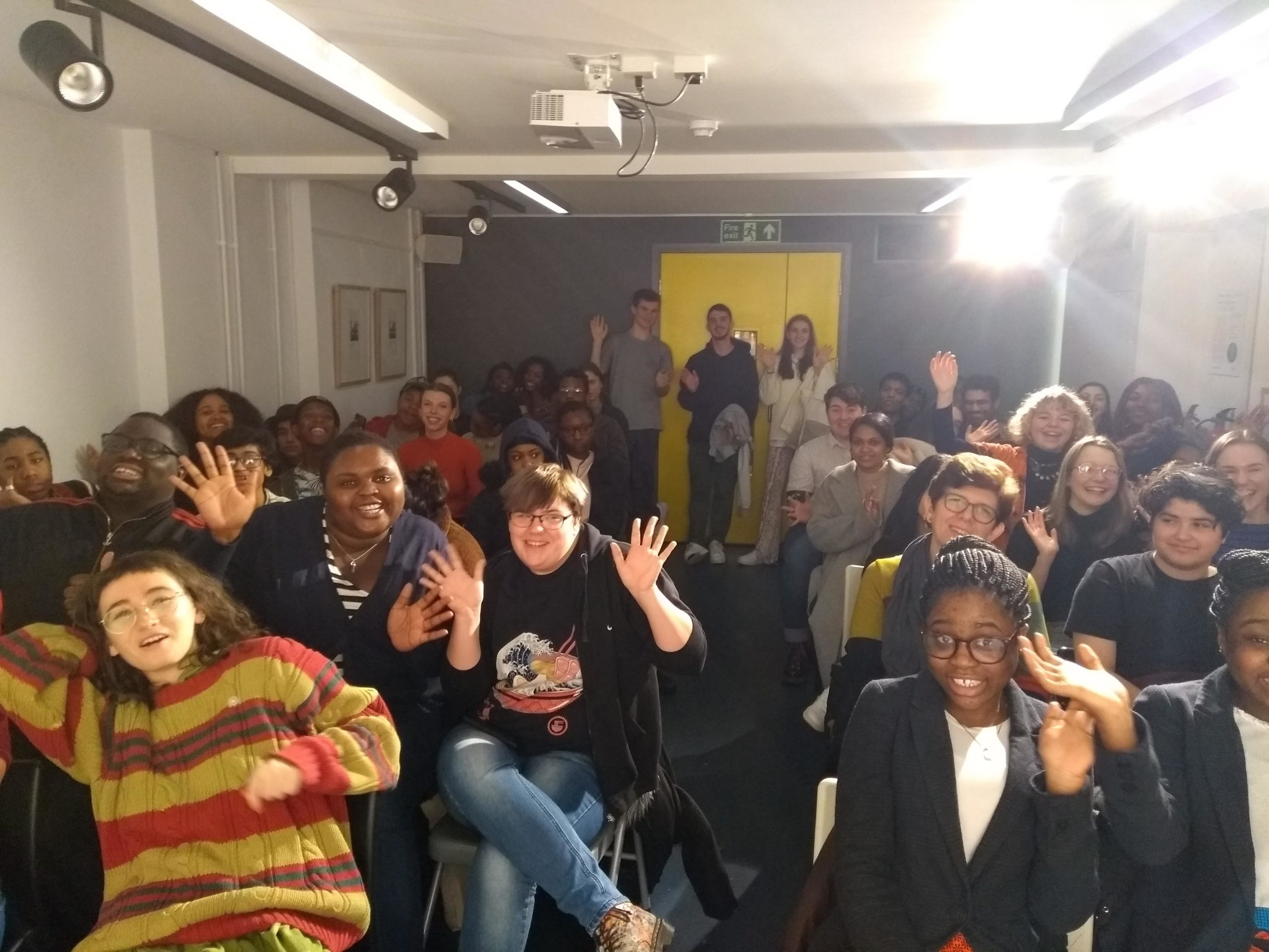 Photo of lots of young people cheering and waving their arms about in The Poetry Café basement