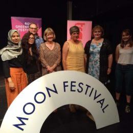 Young Poets Networkers and members at the Moon Festival standing behind a rainbow-shaped banner on the floor that reads MOON FESTIVAL