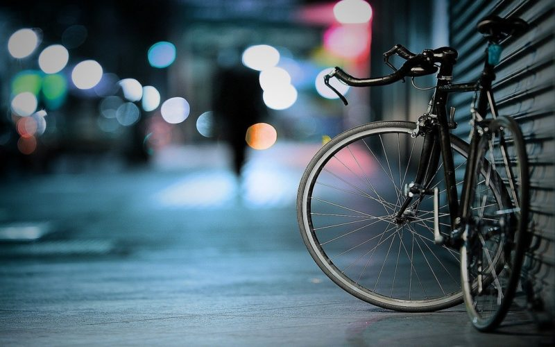 front wheel of bicycle on a street with streetlights