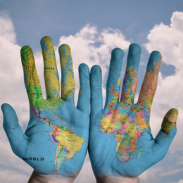 two hands covered in a map of the world, with a background of clouds