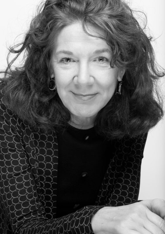 A black and white portait photograph of the US poet Mary Ruefle, who looks directly into the camera with a quizzical smile.