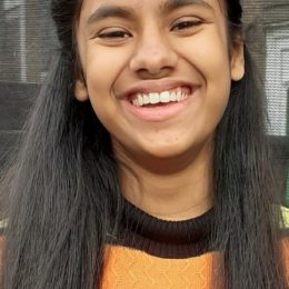 Evie Alam, wearing a black jumper with thick orange stripes, smiles