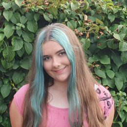 Jenna Hunt, with a blue streak in her hair and a pink top