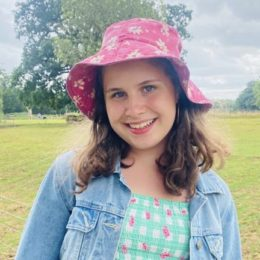 Lulu Marken, wearing a pink flowery hat, a green and white checked top and a denim jacket